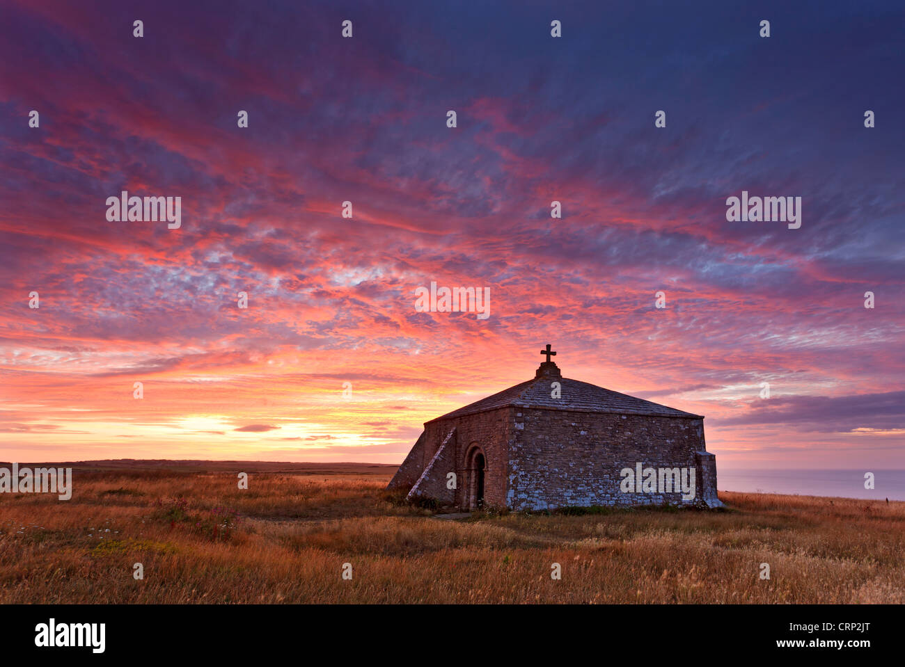 Sunrise over the thirteenth century square shaped St Aldhelm's Chapel near Worth Matravers. Stock Photo