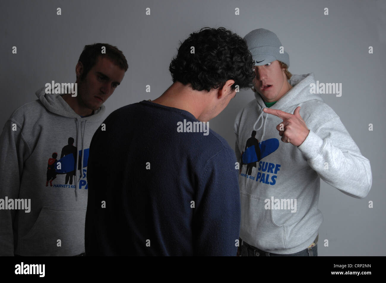 Two angry men confront a young male. - Stock Image