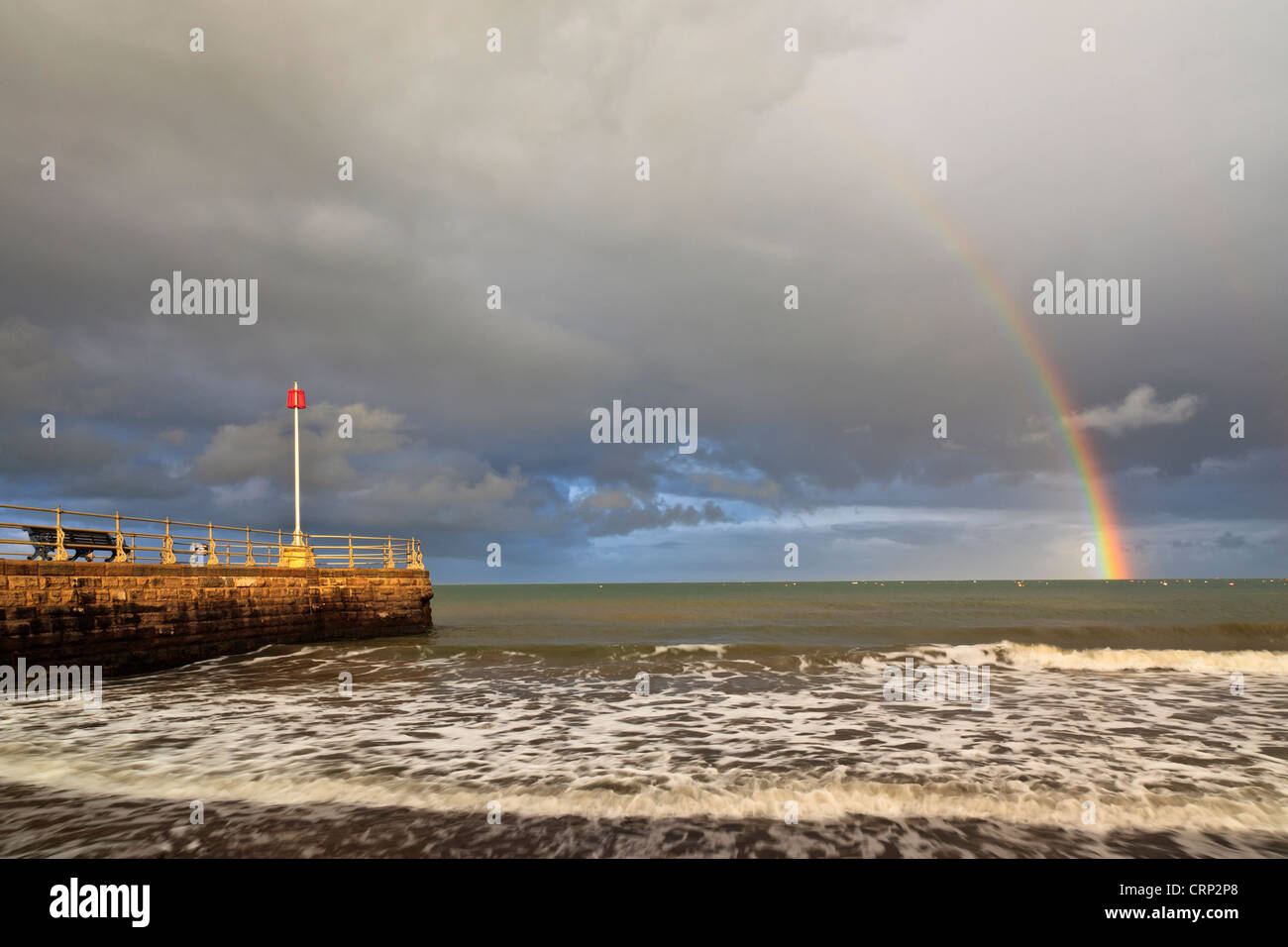 Rainbow over the sea at Swanage with the Banjo Jetty in the foreground. - Stock Image