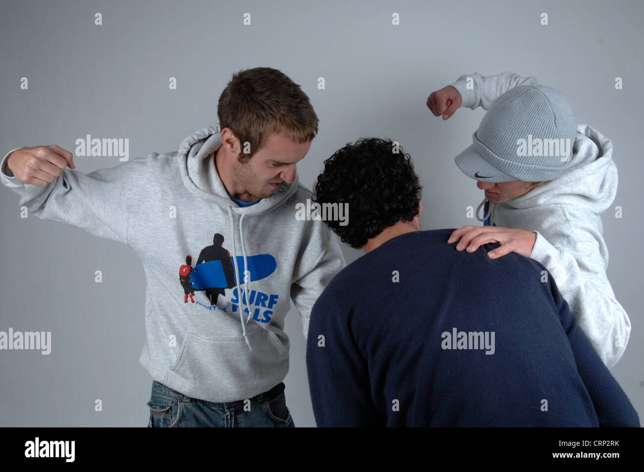 Two young men beating up a young man - Stock Image