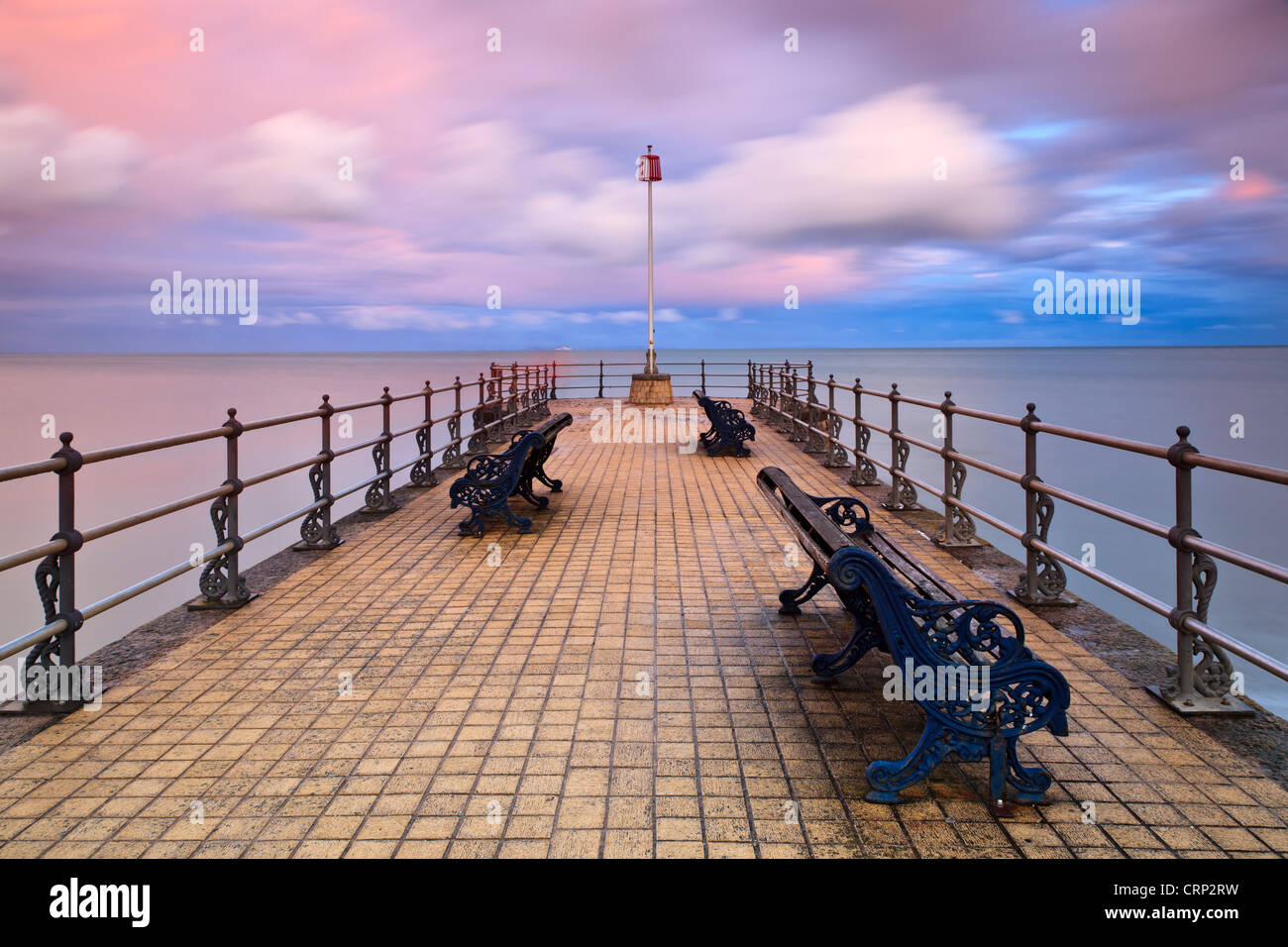 View over benches on the Banjo shaped Jetty in Swanage Bay. - Stock Image
