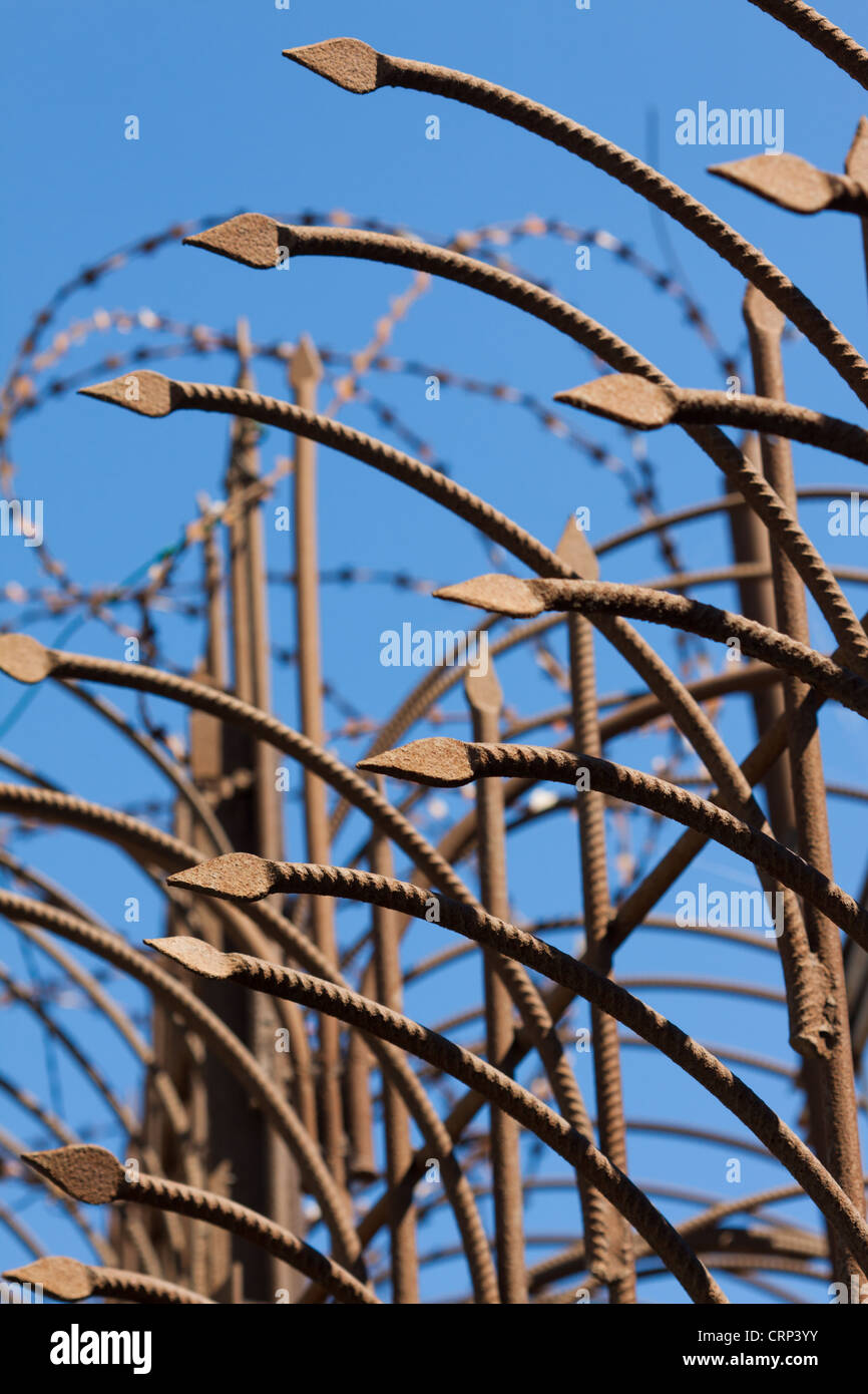 Fence with sharp iron pikes and barbed wire - Stock Image