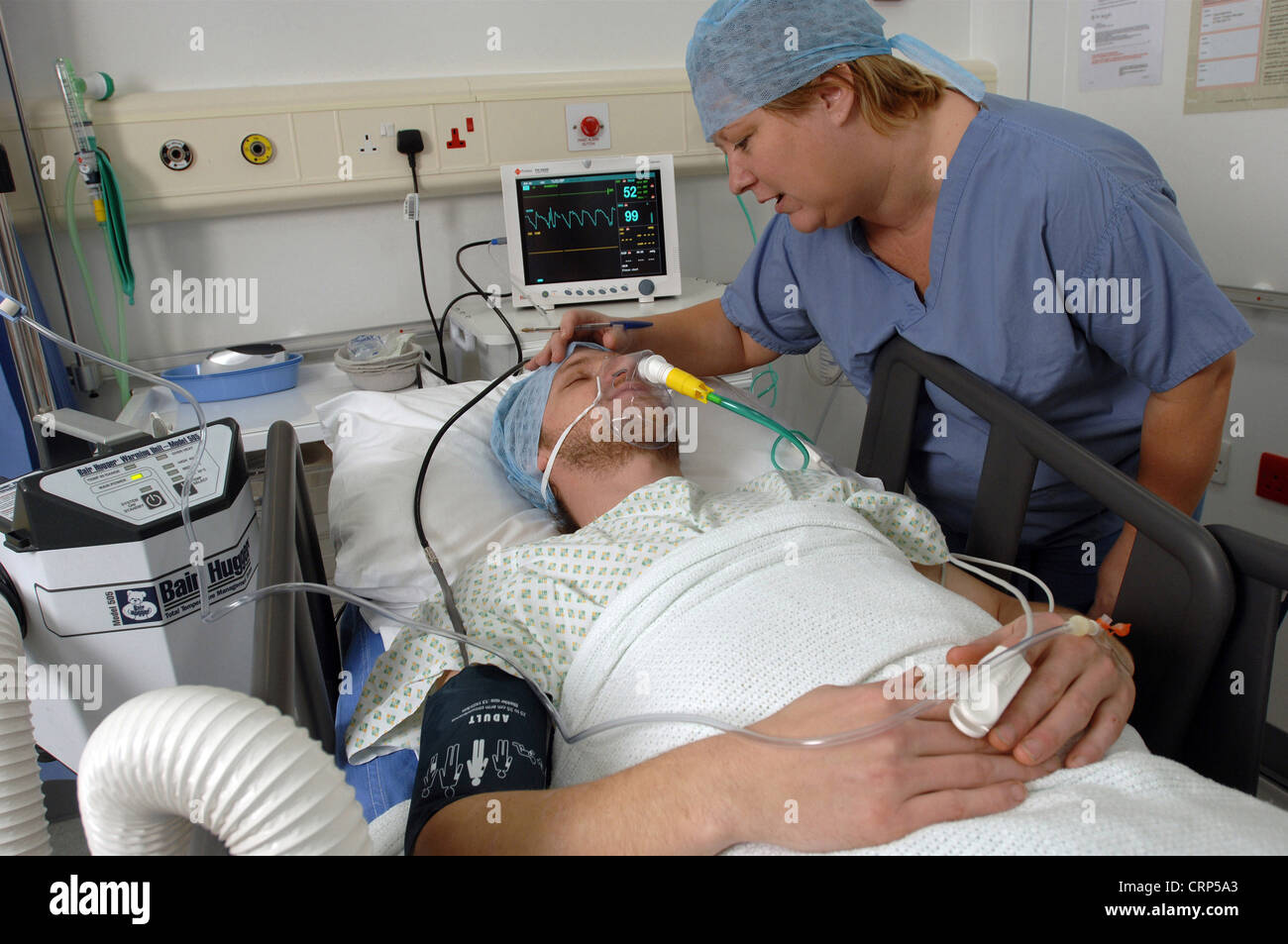 An anaesthetised patient is checked by a female anaesthetist whilst wired to electronic equipment to monitor his - Stock Image
