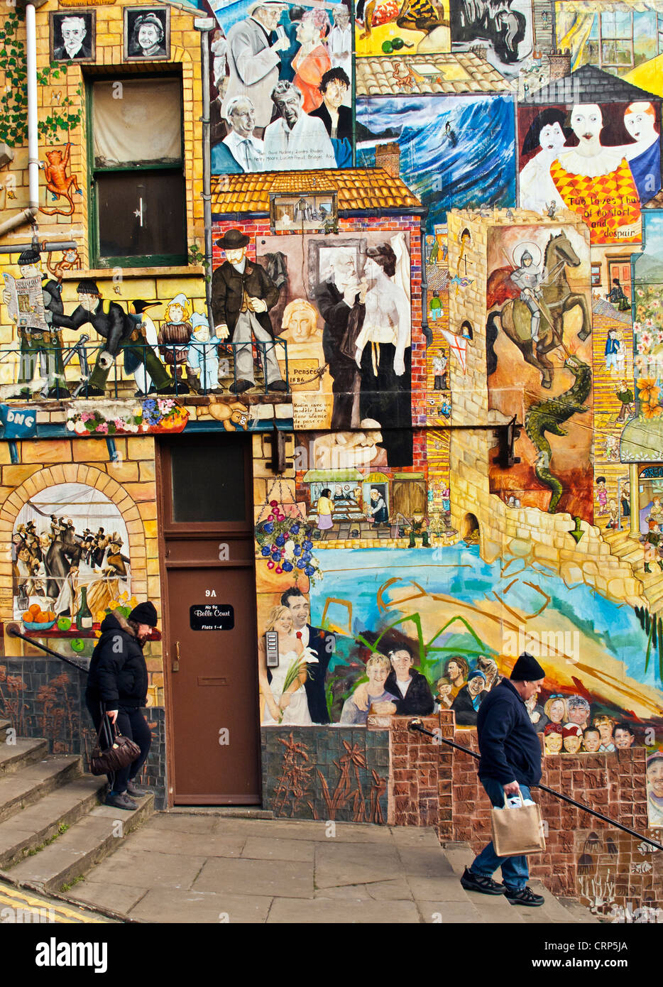 Two people descending flights of steps at Blands Cliff in front of wall murals painted by local artists. - Stock Image