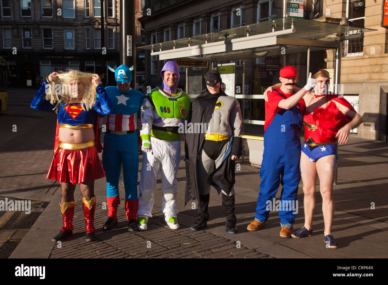 A group of men dressed as super heros and animated characters on a stag weekend. Stock Photo