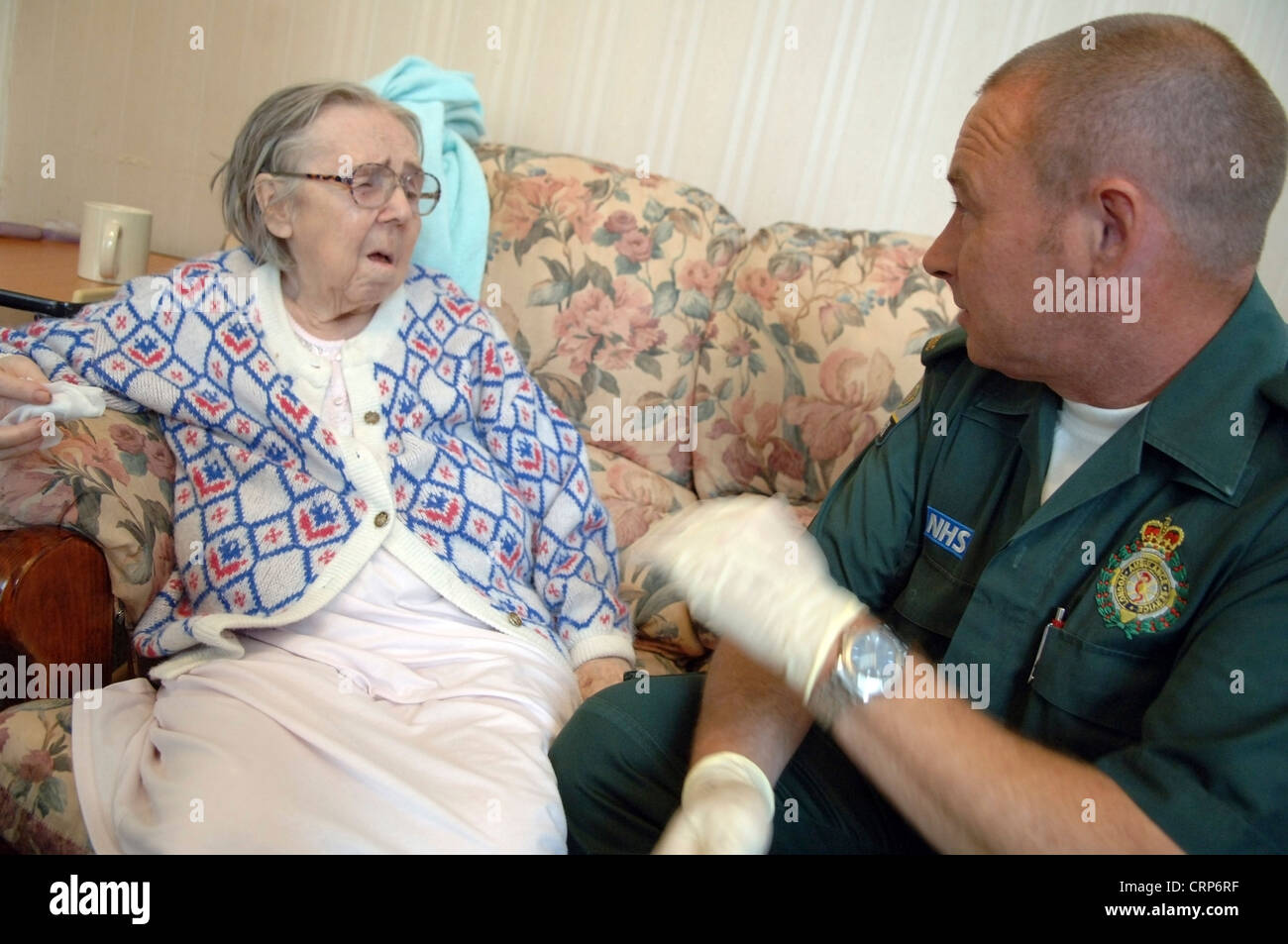 A paramedic from the NHS London Ambulance Service caring for an elderly woman. - Stock Image