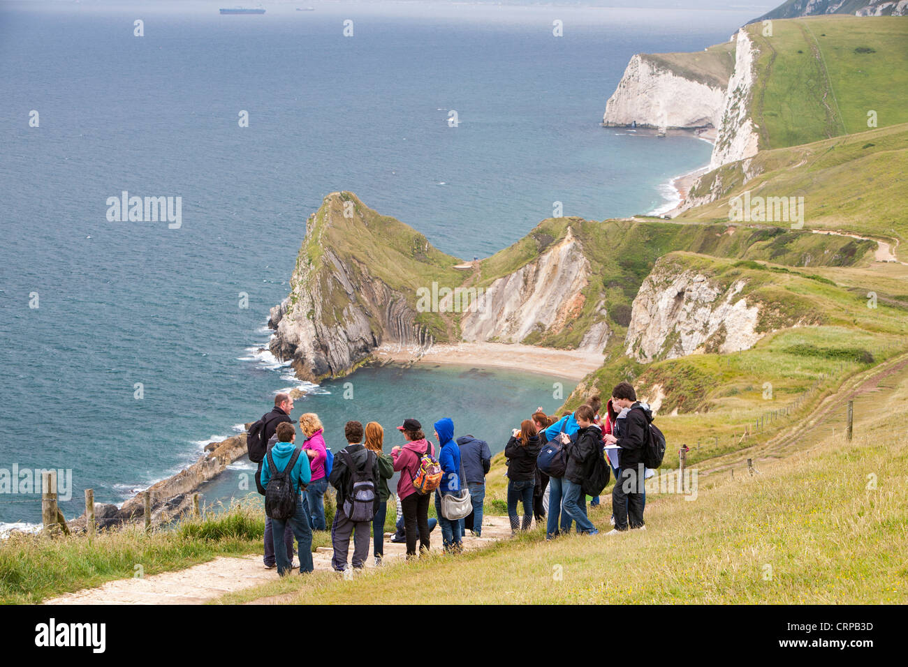 A school field trip on the cliff tops at Durdle Door on the Dorset coast near Lulworth, UK - Stock Image