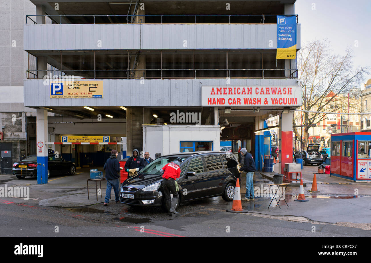 American style hand car wash and vacuum outside a multi-storey car park in Great Eastern Street in the East End - Stock Image