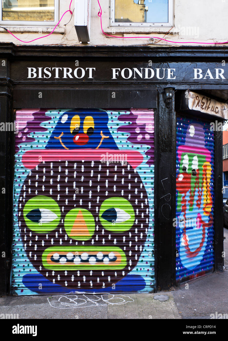 Colourful pictures painted on the shutters of Bistrot Fondue Bar in the East End of London. - Stock Image