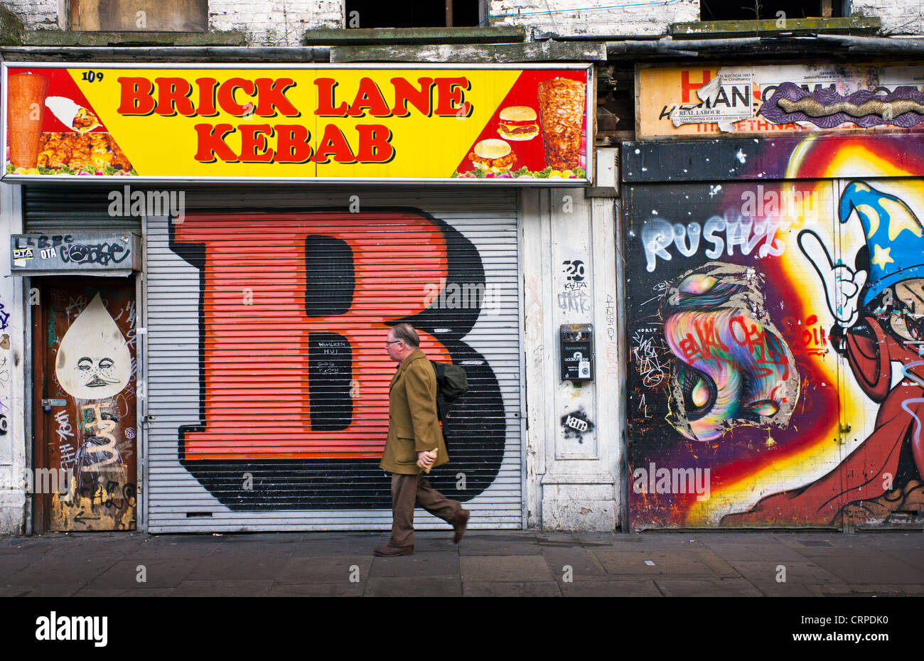 A man walking to work past shopfronts covered in graffiti on Brick Lane in the East End of London. - Stock Image