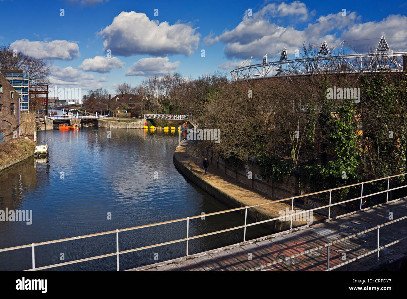 The Greenway footpath and cycleway crossing the river with the Olympic Stadium in the background. - Stock Image