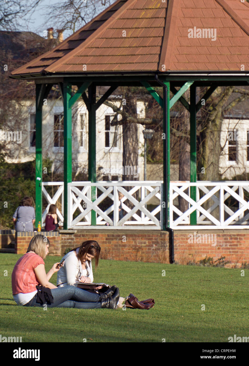 Two young women relaxing on the grass in front of the bandstand in  Parson's Close Recreation Ground. - Stock Image