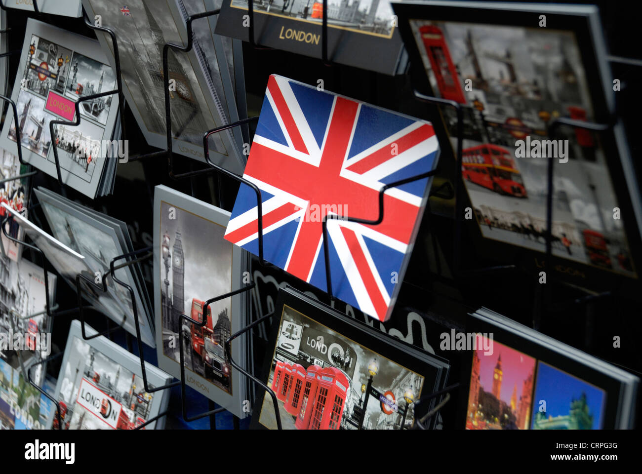 Postcards featuring London icons and a Union Flag on display in a rack. - Stock Image