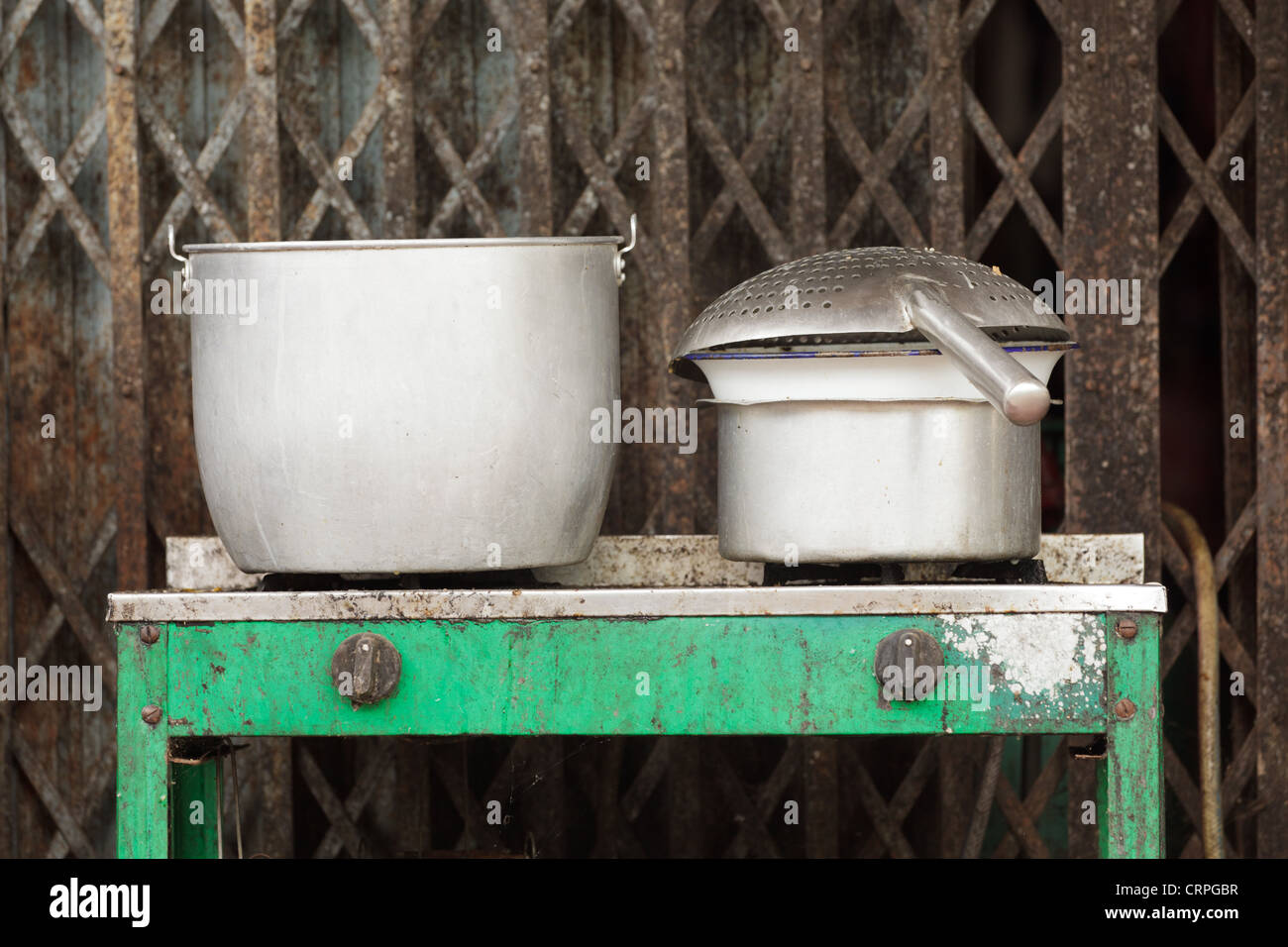 Old gas stove with aluminium cauldrons and wok, Vientiane, Laos - Stock Image