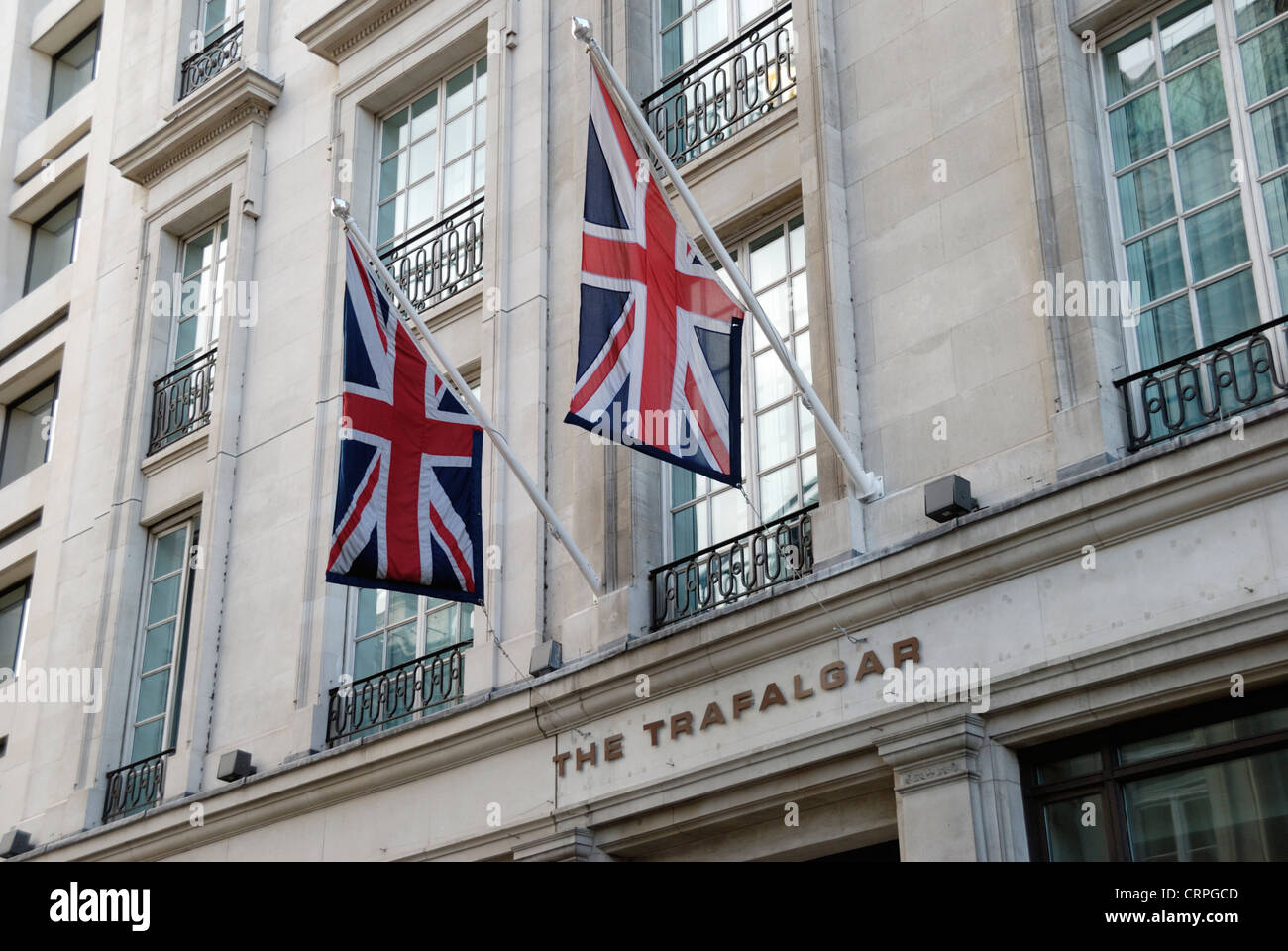 Union flags outside The Trafalgar Hotel on the south side of Trafalgar Square. - Stock Image