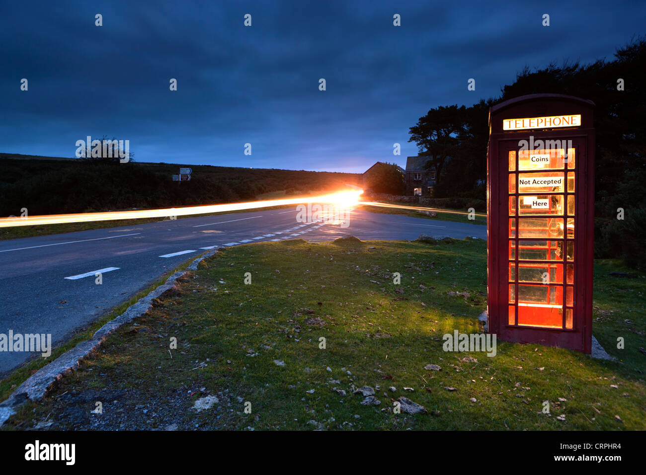 Light trail from a car passing a red telephone box by the side of a road in Dartmoor National Park. - Stock Image