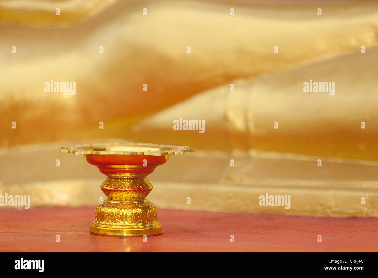 Golden cup containing water offering in buddhist temple, Thailand Stock Photo