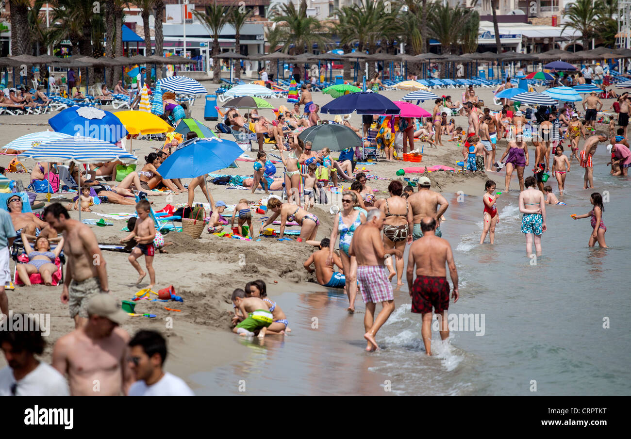 A crowded beach scene in the seaside town of Javea on the Costa Blanca, Spain. - Stock Image