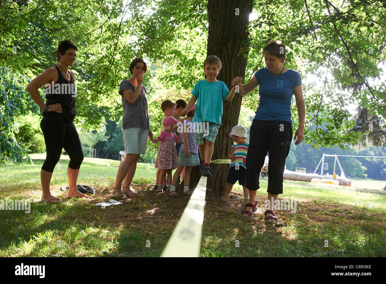 Children and Parents Slacklining in summer park - Stock Image
