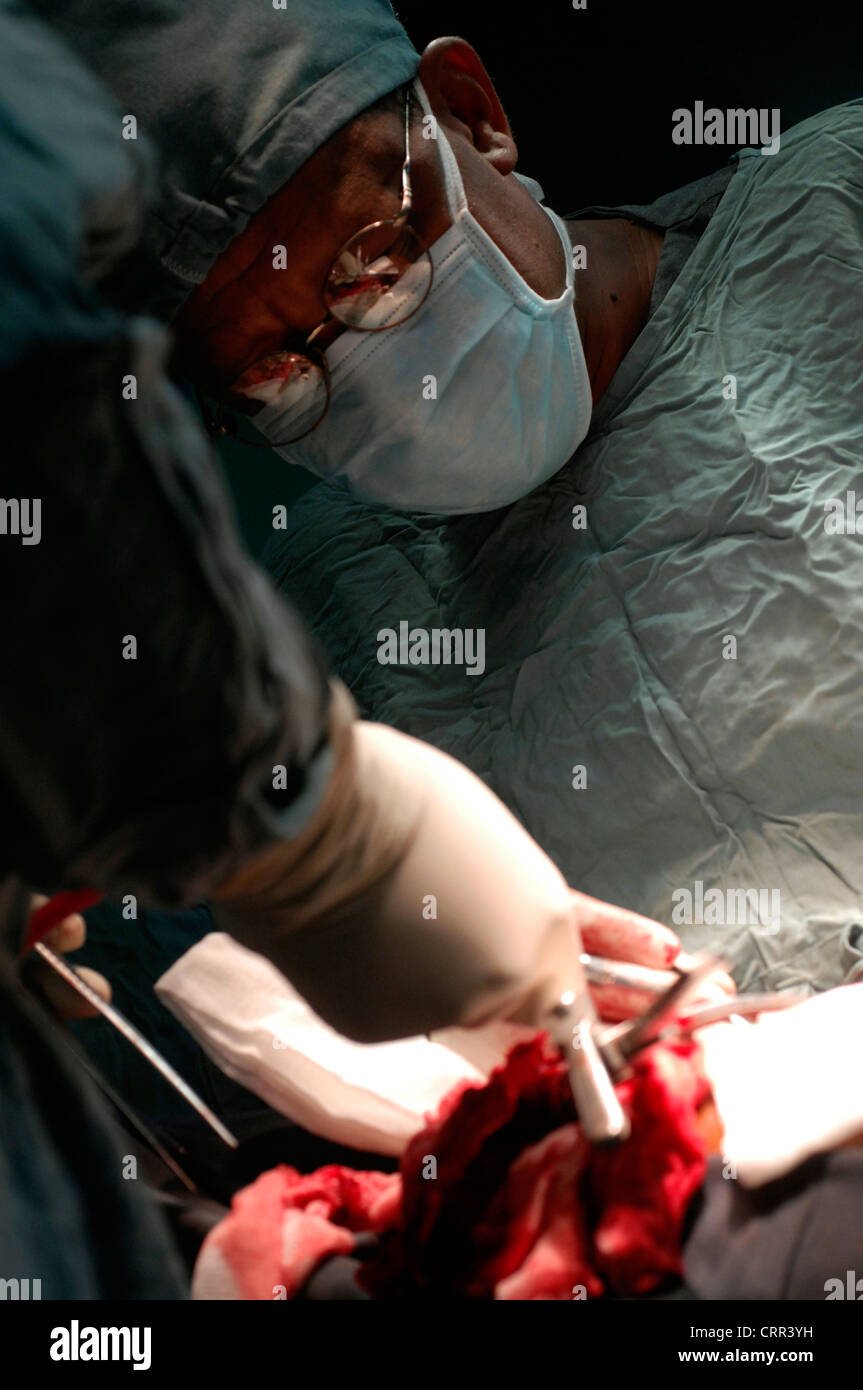 Surgeon and his assistant operate on a patient. - Stock Image