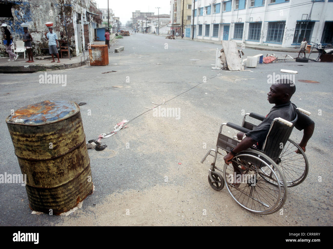 Liberia, a wheelchair in front of a roadblock - Stock Image