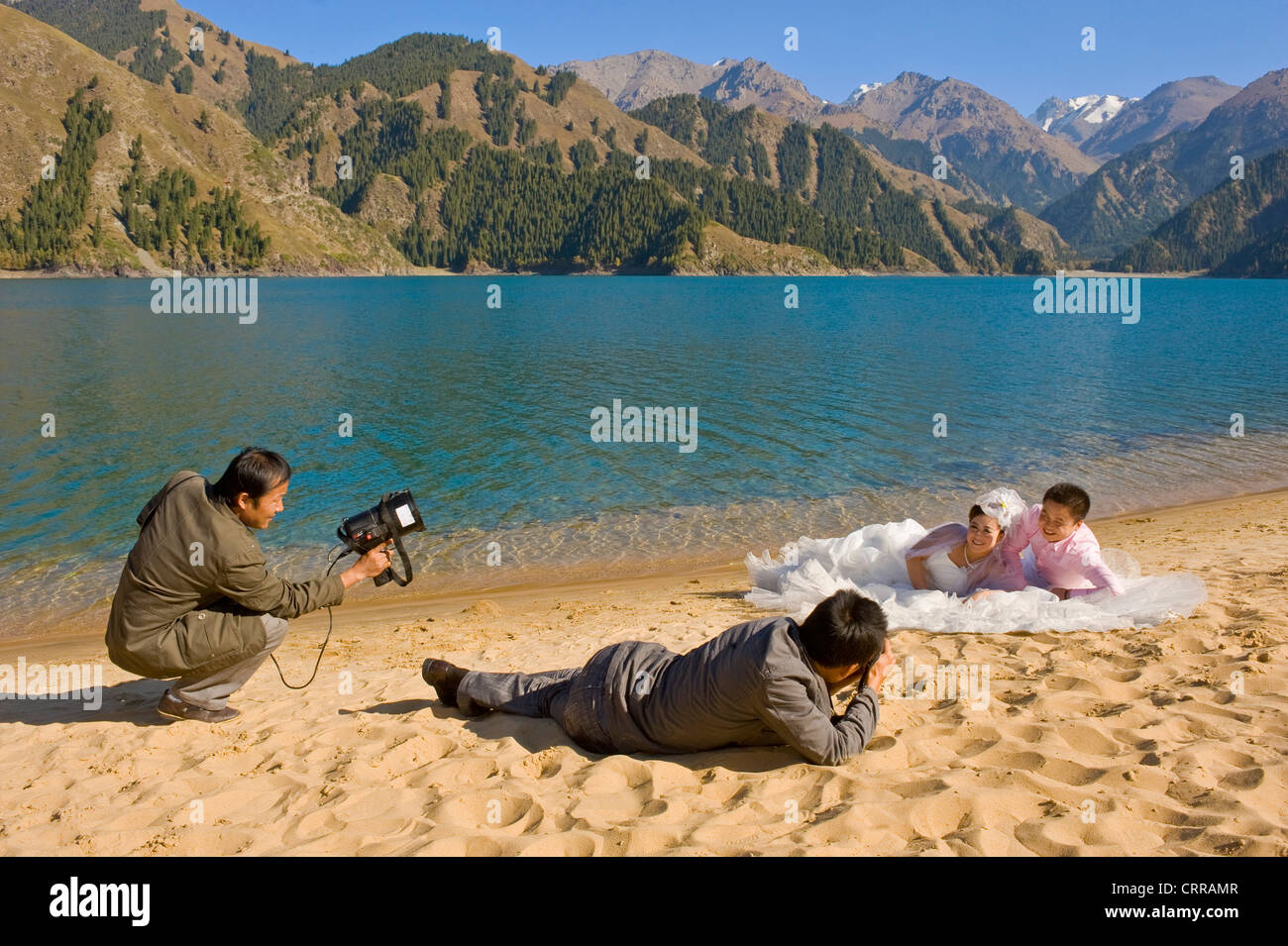 A Chinese couple pose for their wedding photographs at the popular alpine beauty spot of Heavenly Lake. Stock Photo