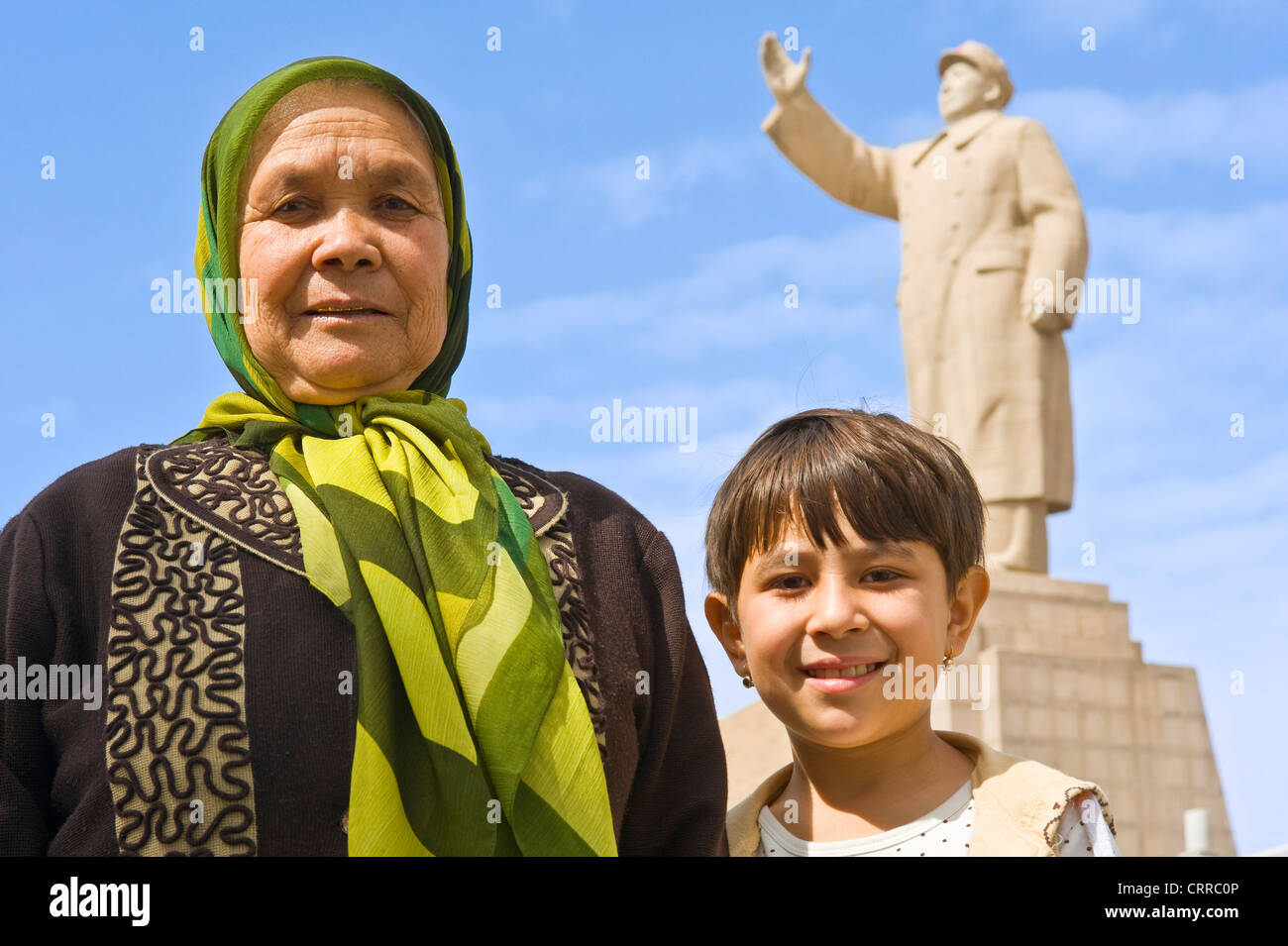 An Uyghur Chinese mother and her child pose for the camera with the statue of Mao Zedong behind in Kashgar. - Stock Image