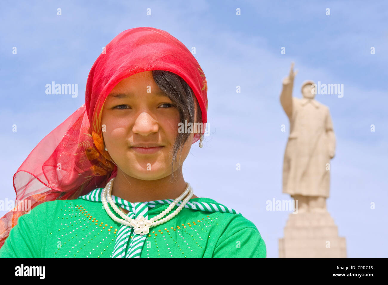 A young Uyghur Chinese girl pose for the camera with the statue of Mao Zedong behind in Kashgar. - Stock Image