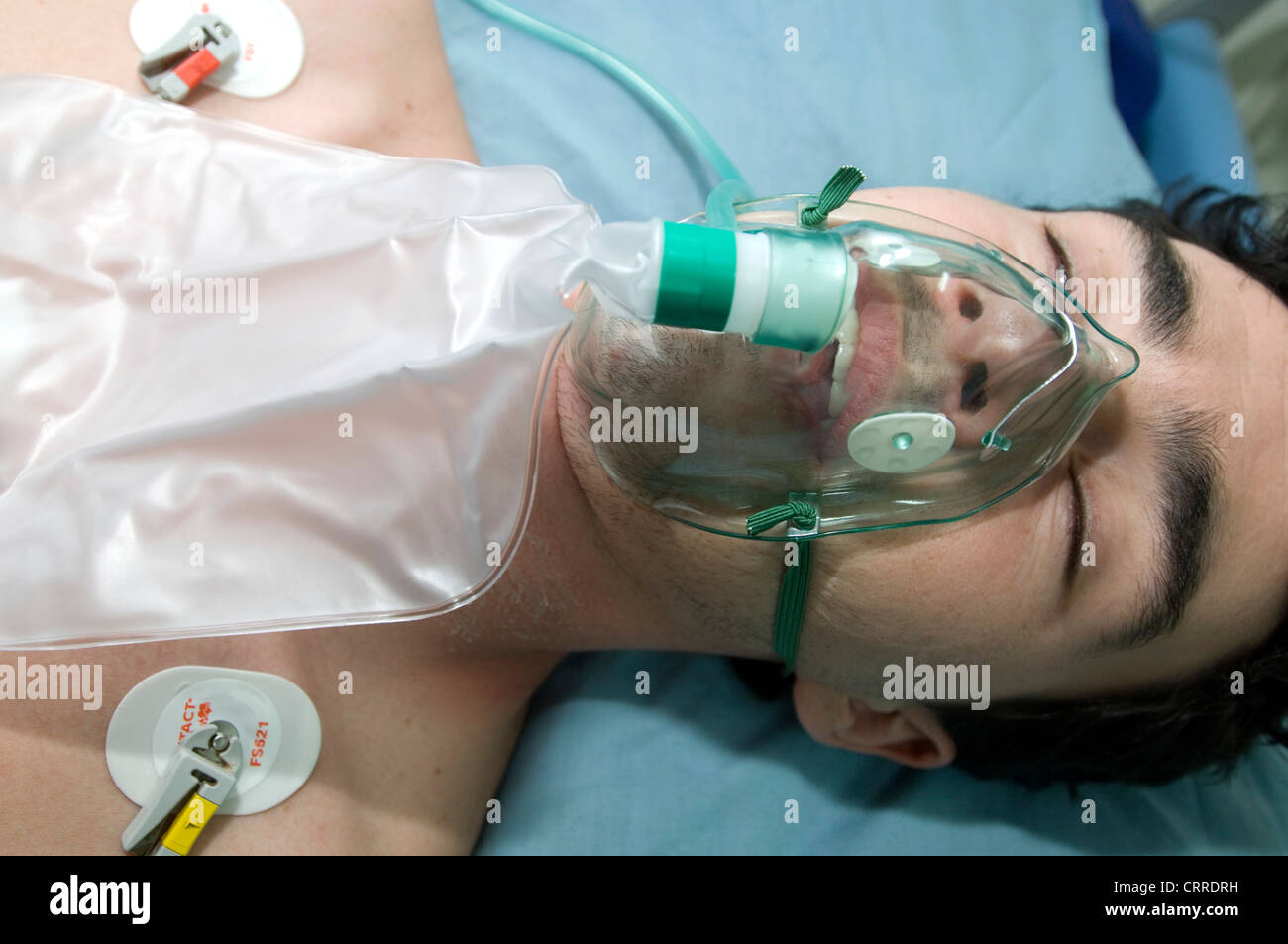A patient with a compromised ability to inhale is given oxygen via a face mask enabling him to breathe more easily. - Stock Image