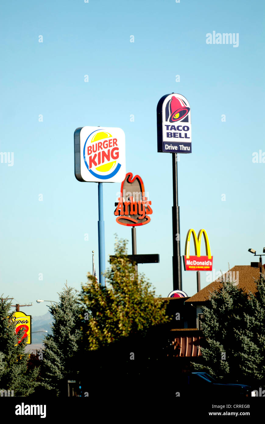Giant signs advertising fast food chain restaurants tower above highway in Ellensburg Washington State USA Stock Photo