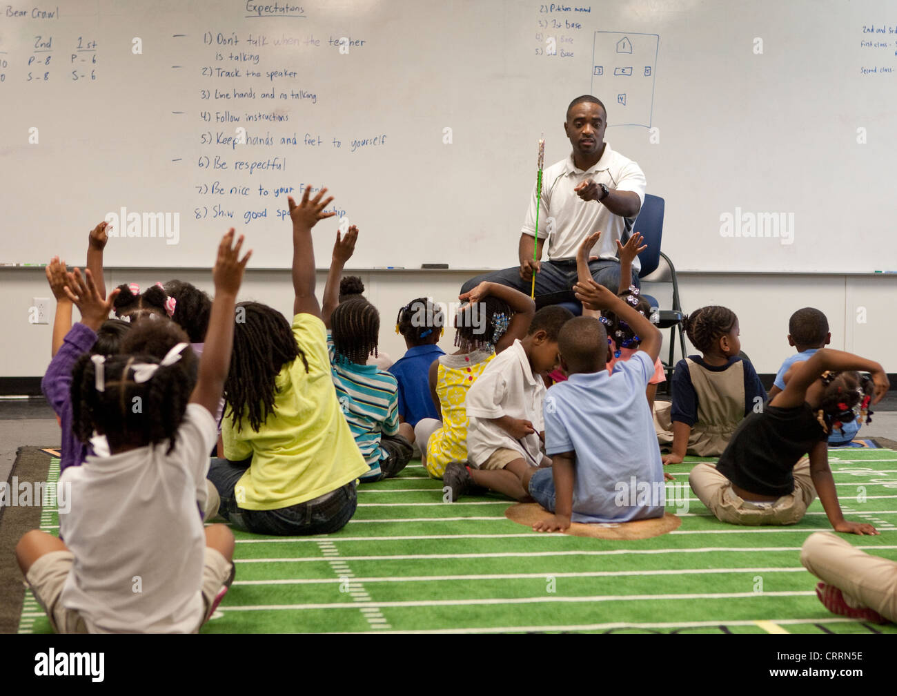 African-American male kindergarten teacher in class with students head start program at public charter in Texas - Stock Image