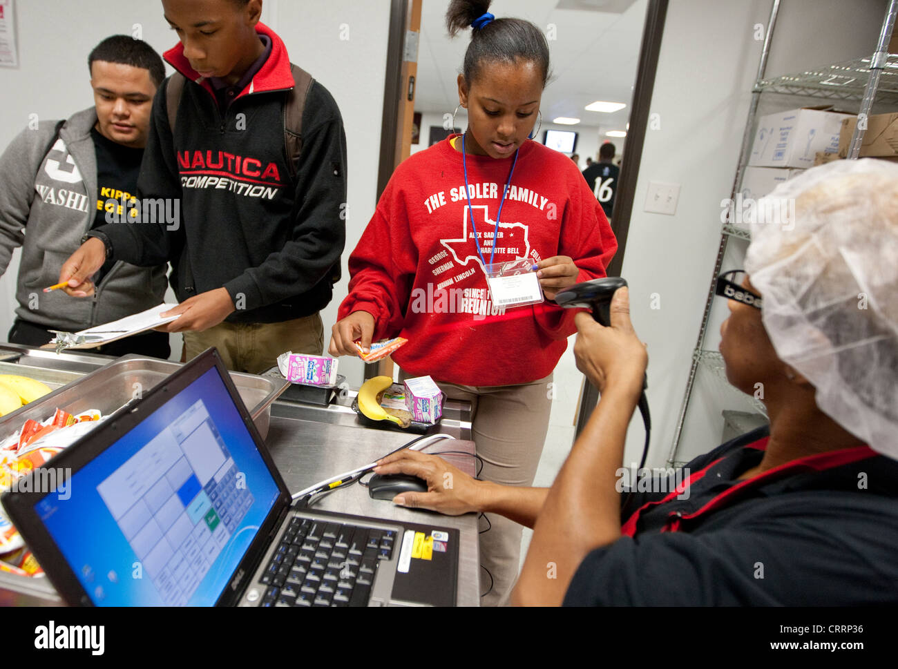 Cafeteria worker uses hand-held scanner to read barcode information on students school lunch cards at public charter - Stock Image