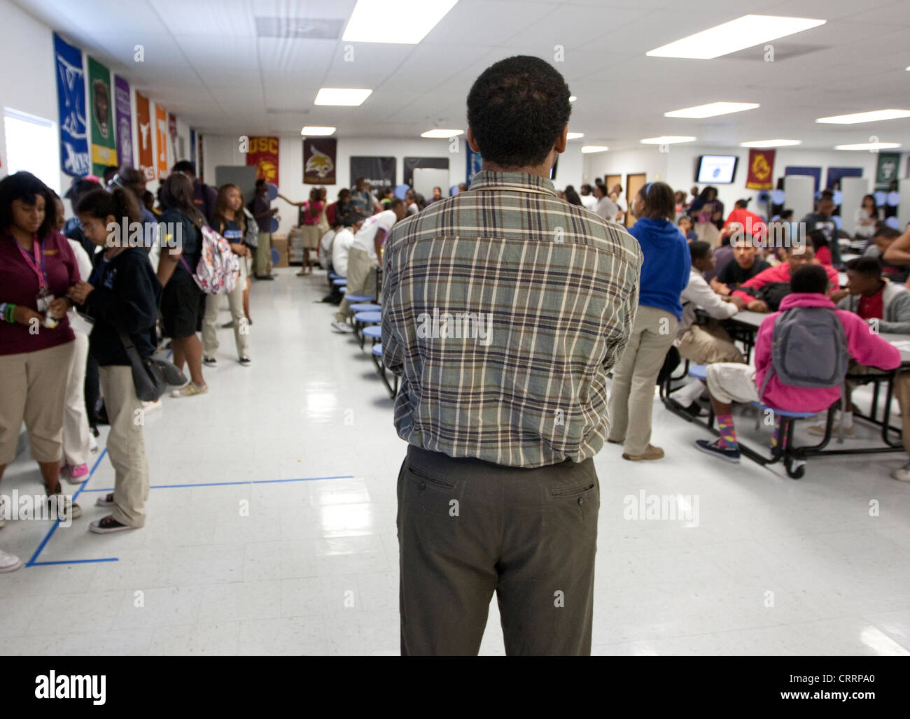 Male African-American teacher serves as monitor during lunch at a public charter high school in Houston, Texas - Stock Image