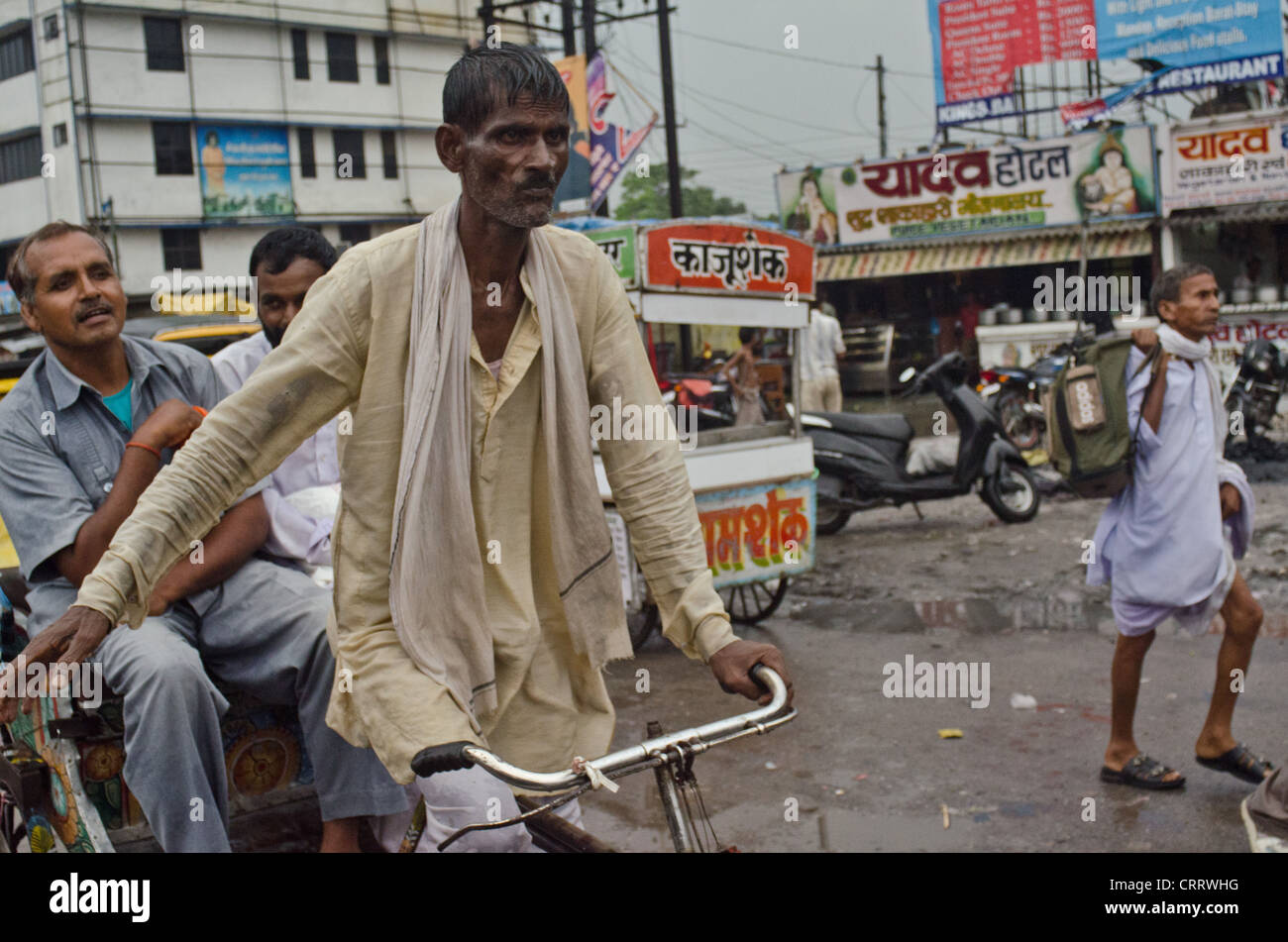 A low cast rickshaw driver carries a two passengers in Gorakhpur, India. - Stock Image