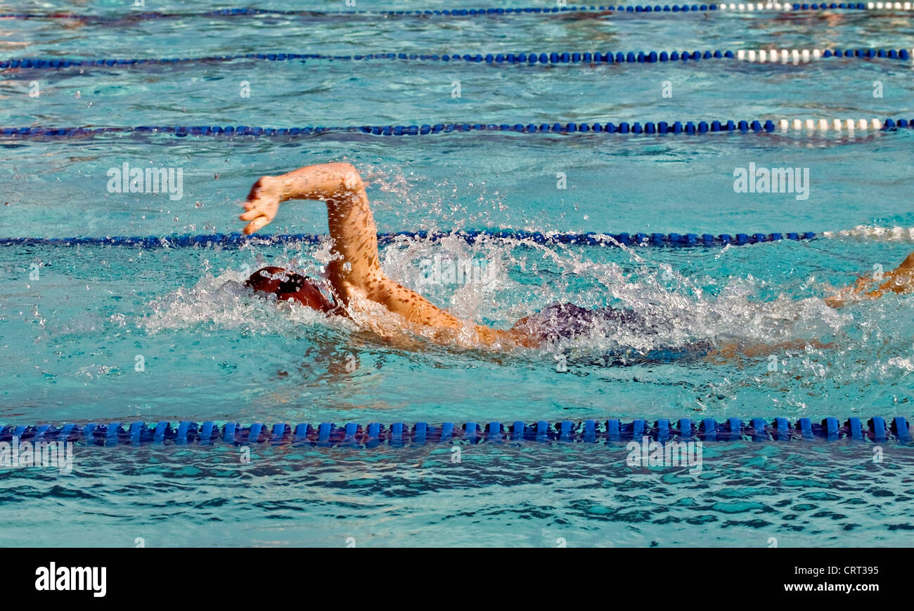 A boy swimming freestyle during a competition swim meet. - Stock Image
