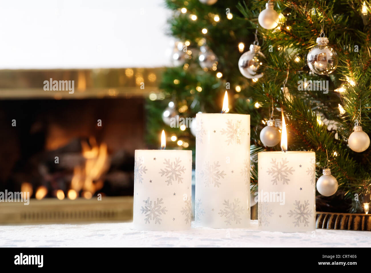 Snowflake candles and glittering decorations by a warm fire Stock Photo