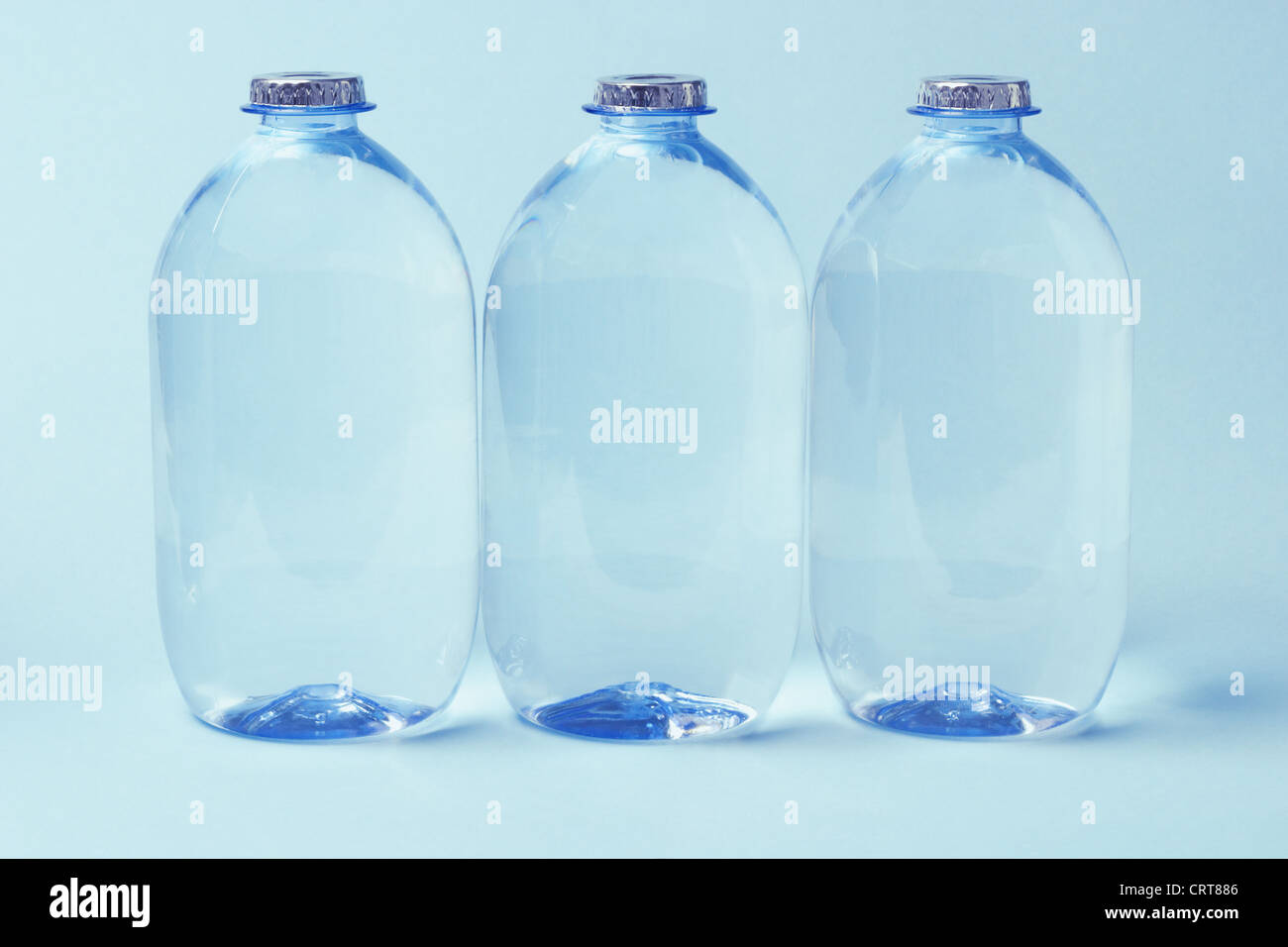 Three Plastic Bottles of Mineral Water on Blue Background - Stock Image