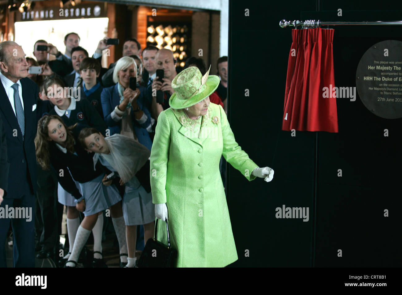 Children look on as Her Majesty The Queen unveils a plaque in commemoration of the opening of the Titanic Building, Stock Photo