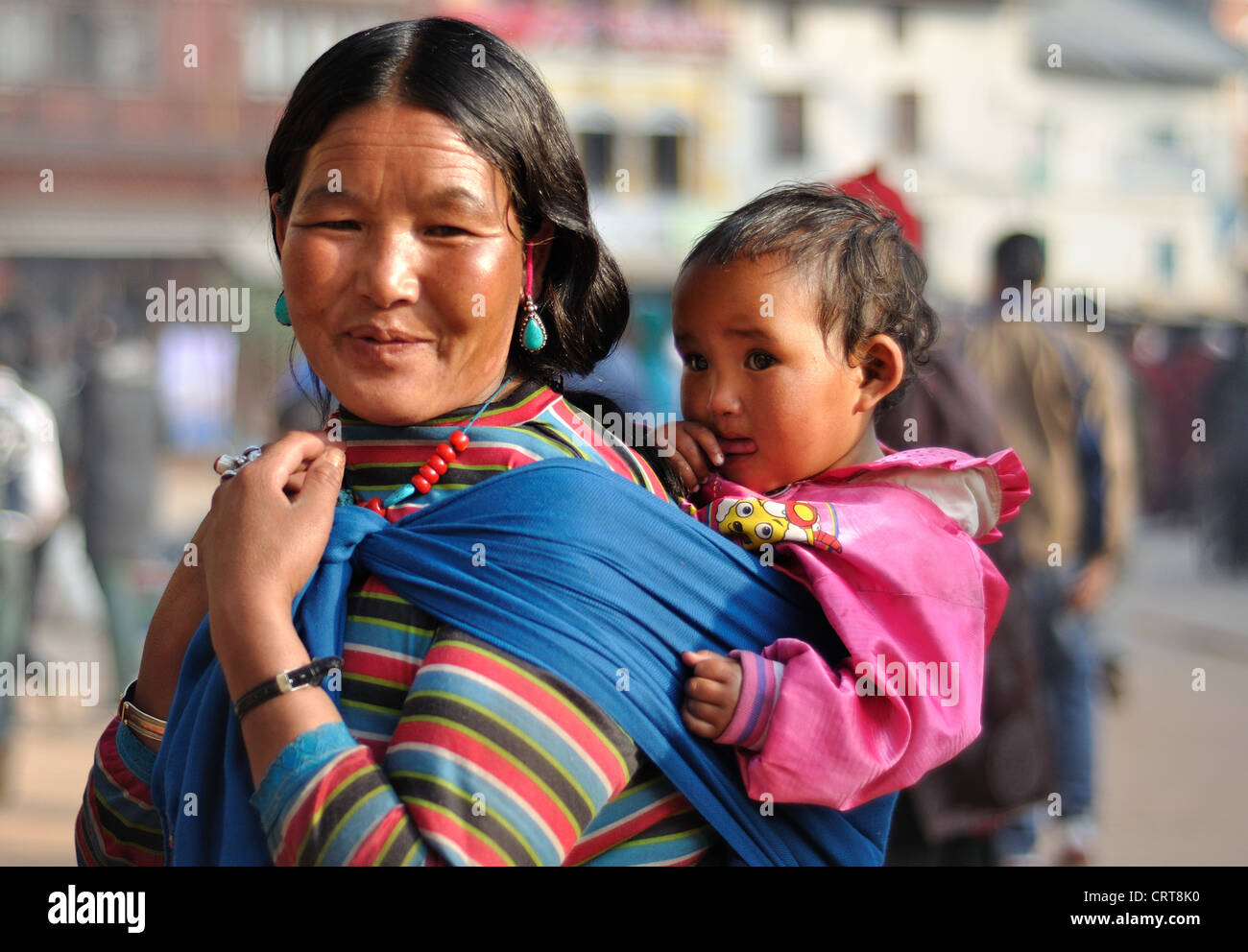 Nepali Mother wearing traditional dress carries her little girl at the holy Boudhanath Site, Kathmandu - Stock Image
