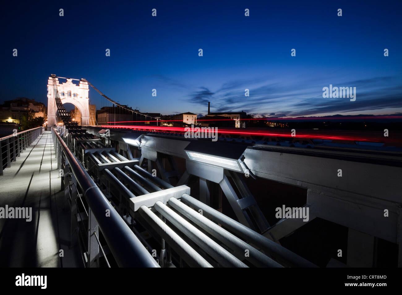 Amposta, Tarragona. Spain -31 Mar 2010- The suspension bridge over the Ebro river at dusk Stock Photo