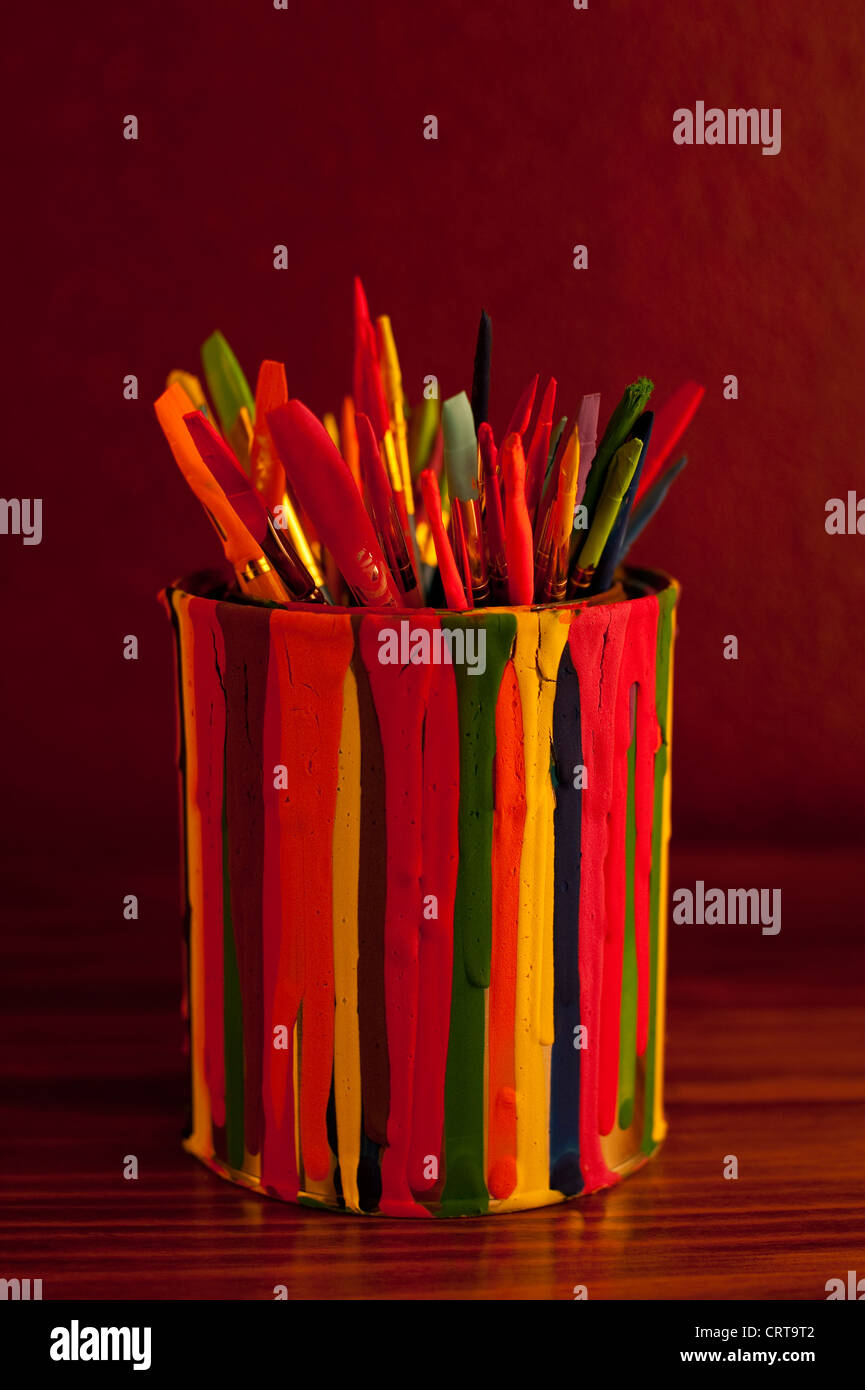 Multicolored paint brushes in a paint can covered with paint drips - Stock Image