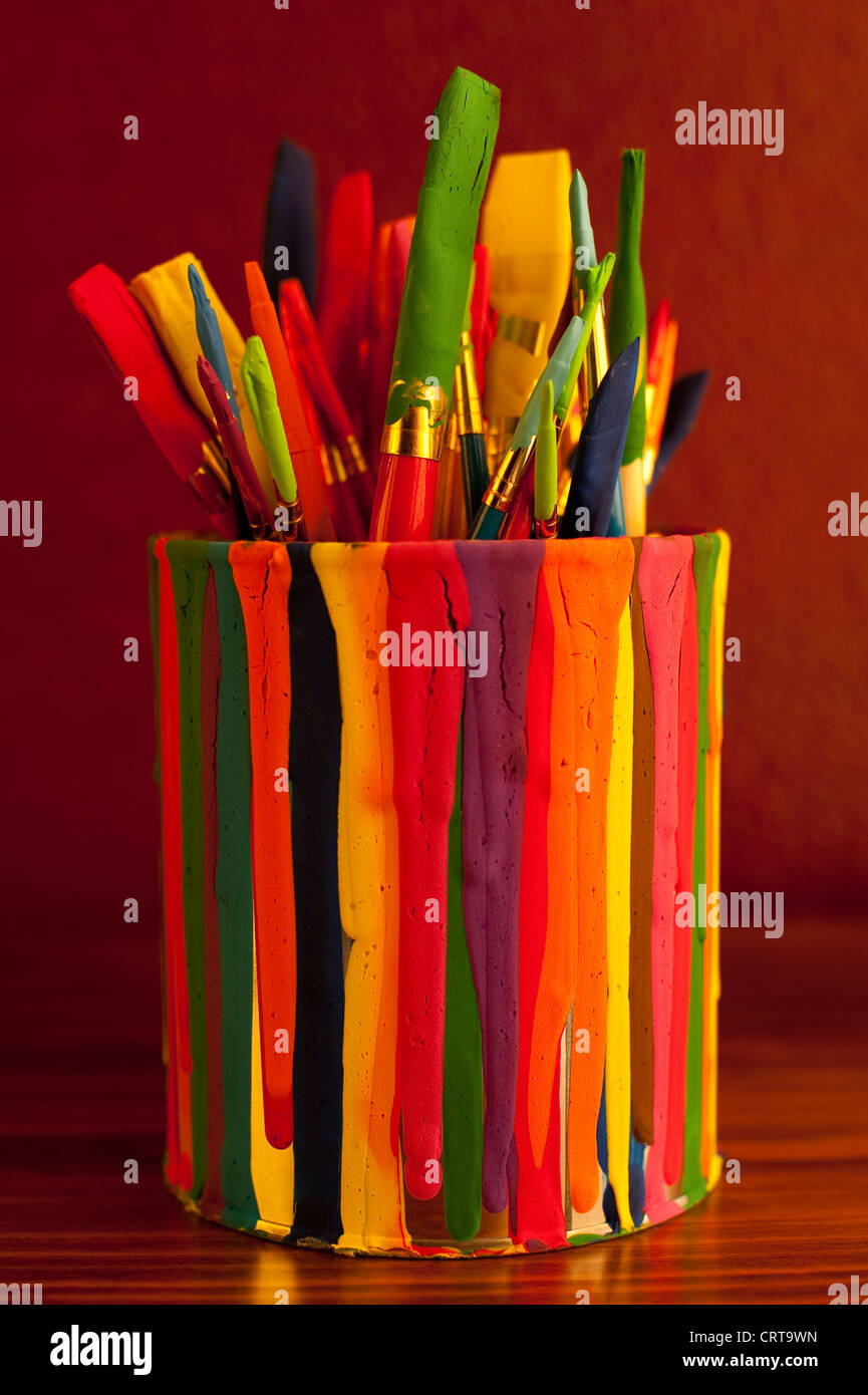 Still Life paint brushes in paint can on desk - Stock Image