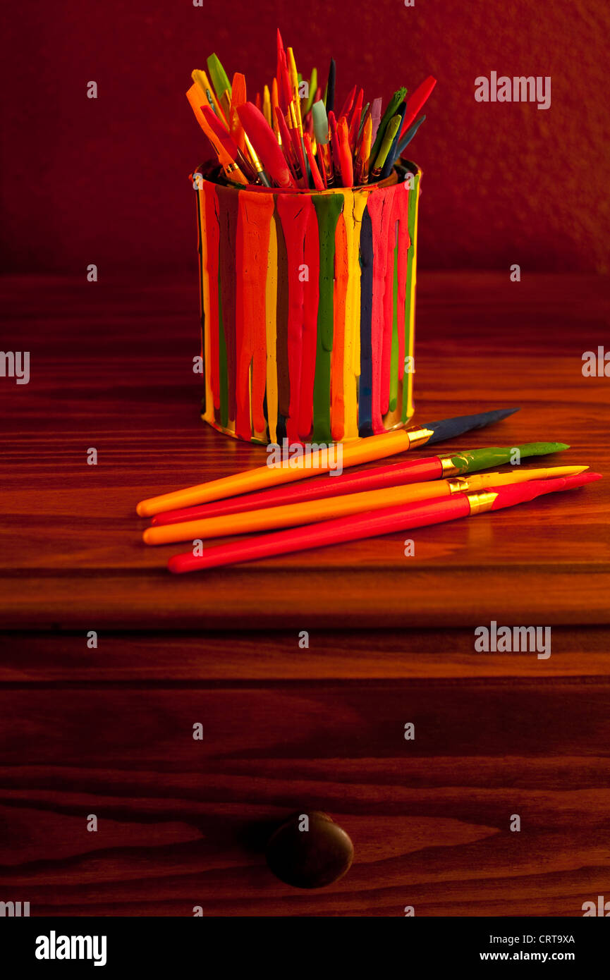 Paint Brushes in a paint can on desk still life studio image - Stock Image