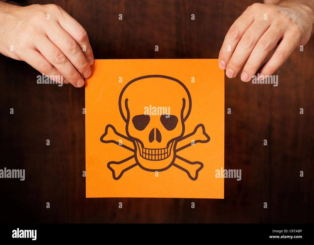 Man holding a warning sign for poison. - Stock Image