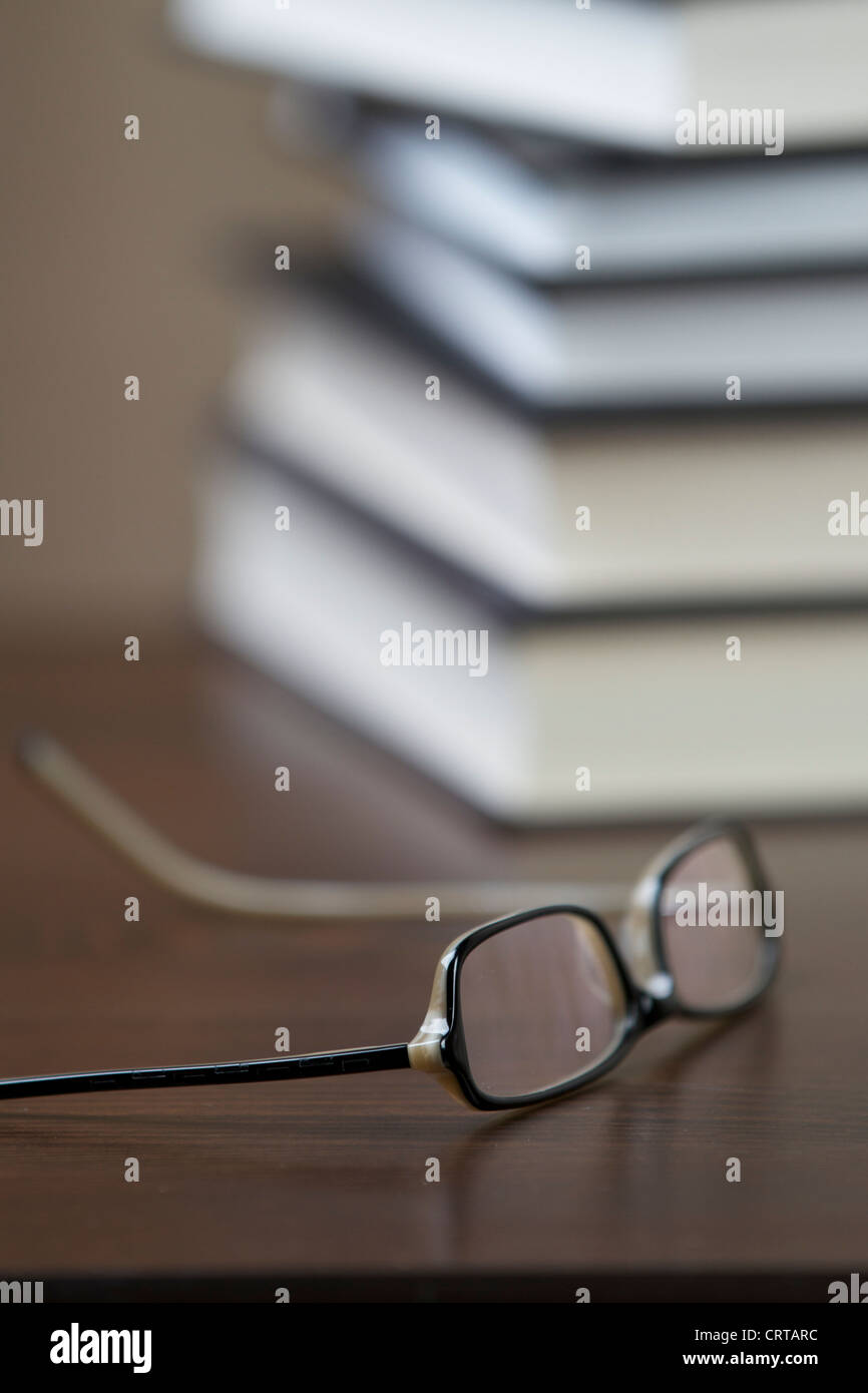 Eye Glasses On Coffee Table Next To Pile Of Books Stock Photo