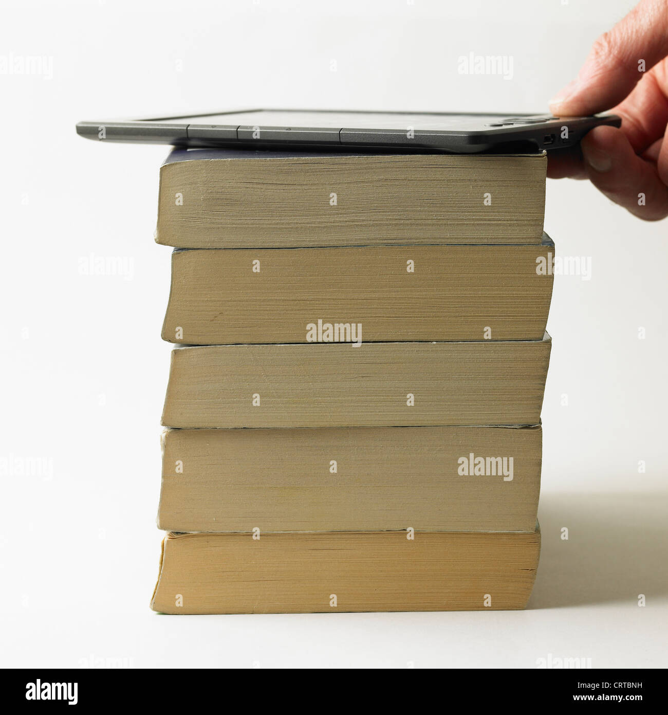 Electronic book on top of a pile of paperbacks - Stock Image
