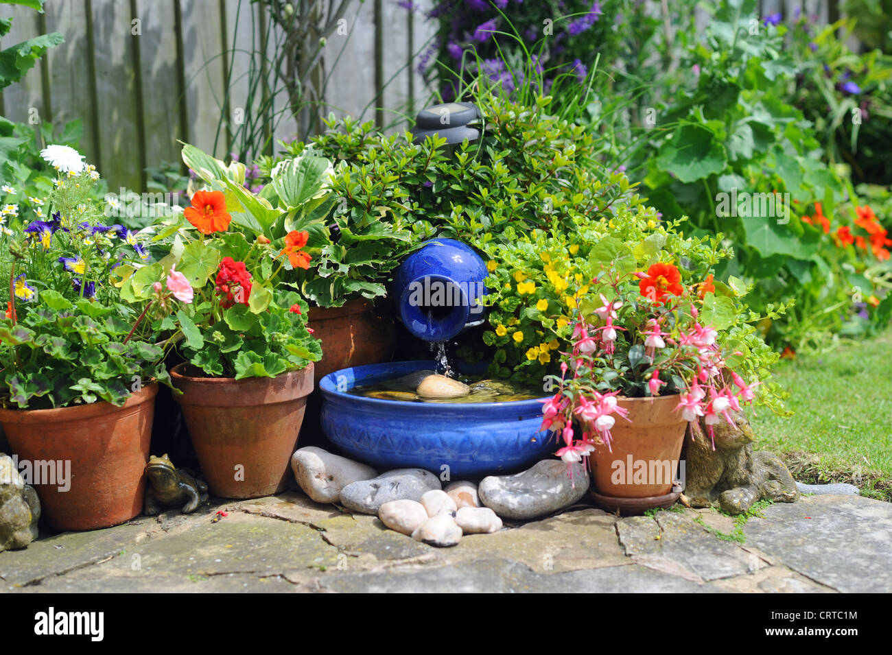 Solar powered garden water feature blue bowl by pot plants UK & Solar powered garden water feature blue bowl by pot plants UK Stock ...