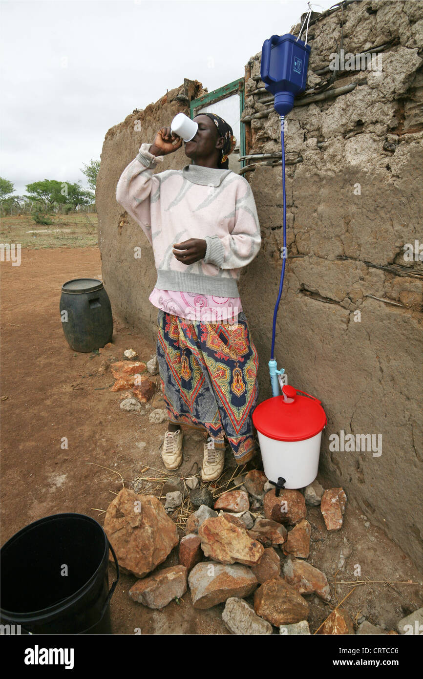 Woman drinking purified water filtered through a family Lifestraw, Swaziland, Africa Stock Photo