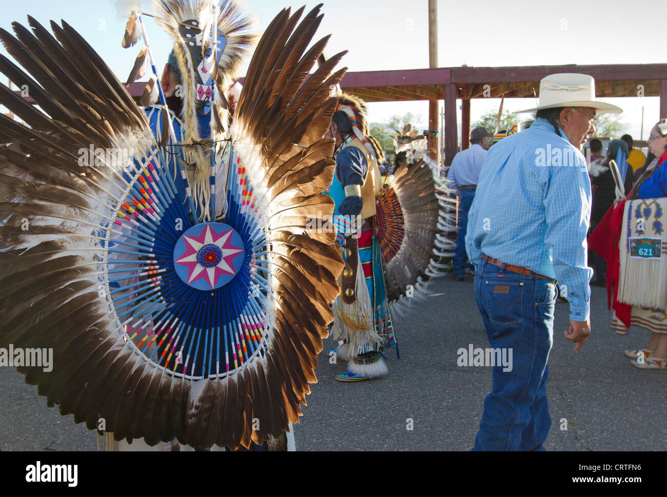Fort Washakie, Wyoming -  Young participant in a powwow checking the regalia of an adult dancer during the Indian - Stock Image