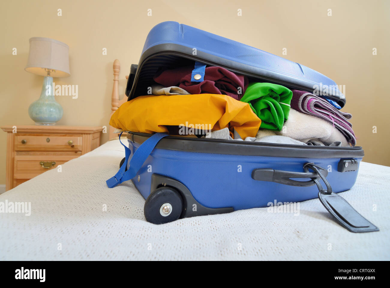 overflowing luggage on a bed - Stock Image